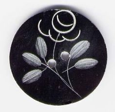 Bone Button #0132. Each button is hand etched with plant leaves, and what appears to be a flower.    Sold in a package of 4 buttons.    Dimensions:  1 inch across. $4.15