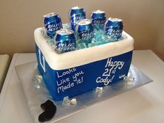 2 layers of cereal treats and two layer 9x13 white cake with Snickers buttercream filling. Covered with fondant and airbrushed blue. Ice is jello made with flavored water. Beer cans are real (emptied from the bottom). The little pair of black socks is bec