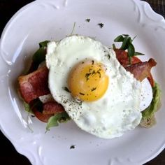 BLT Avocado Toast, a simple brunch recipe that combines avocado toast with a BLT and a sunny side up egg - via The Kittchen