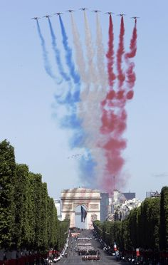 The Patrouille de France aerobatic team fly over the Champs Elysees avenue to open the Bastille Day military parade in Paris