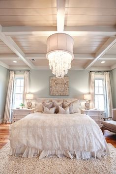 Tall light curtains. Chandelier above bed. Nightstands with lamps on each side of bed. Rug under bed