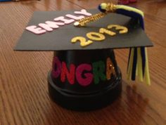 Congrats Graduate!! Clay pot, black paint, square piece of card board, pipe cleaners, foam letters and a brad.