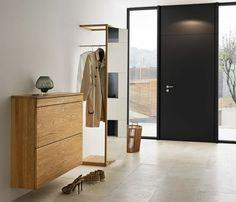 petite console d'entrée en bois clair, sol en carrelage beige et porte d'entrée noire