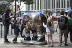 Passer-by look on an elephant sculpture as part of the 'Elephant Parade' at the Paulista Avenue in Sao Paulo, Brazil, Aug. 1, 2017. (Photo: Sebastiao Moreira/EPA/REX/Shutterstock)
