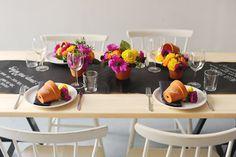 mesa romântica para dia dos namorados com trilho preto para escrever recado e vasinhos de flores.