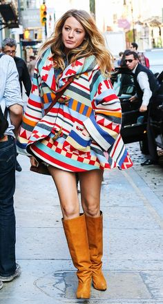 Blake Lively wears a bold printed coat and camel knee-high boots.