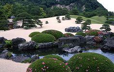 White gravel and pine garden in Adachi Museum Gardens, Yasugi, Japan.  Black pine trees interspersed among the azaleas, rock, and white gravel create a harmonious balance.