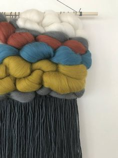 This wall hanging is handwoven in Minneapolis, MN. Colors: gray, navy, white, blush pink, burnt orange, turquoise, and mustard. This wall hanging is 13 inches long, 12 inches wide, and hangs on a 14 inch wooden dowel. It is made with 100% wool roving, and 100& cotton fringe. This item