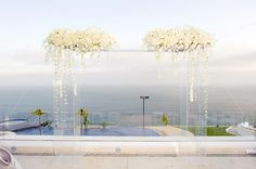 A modern, acrylic ceremony structure allowed guests to enjoy the ocean view. Hoffmann Photographer.