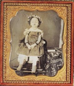 A deceased child positioned in a chair. Often if the body was propped up eyes were either painted onto the eyelids or the photographer would draw eyes onto the photo itself. 1854 saw the advancement in photography of color-tinted ambrotypes, thin negative images on glass made to appear as a positive by showing them against a black background. Ambrotypes sold at less than half the price of a daguerreotype. (This is not an ambrotype of course)
