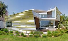 Horizontal slatted white and green siding allows this house to blend into the environment.