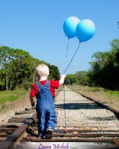 Two-year-old boy with 2 balloons on tracks