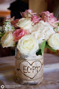 Pink and white rose centerpiece in a vase surrounded by aspen bark with the couple