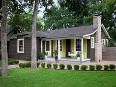 I don't usually like dark colors on a small house because it makes it feel that much smaller. But the cream trim color and yellow shutters really make this house pop.