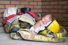 Newborn baby in firefighter gear by Christie Knight Photography