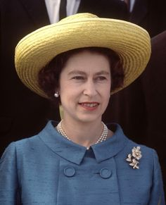 Her Majesty's jackets are rarely seen without a brooch to keep the left lapel or corner company. Shining out like a delicate diamond or pearly beacon, they never fail to gently complement what Queen Elizabeth is wearing.  Here, the Queen matches a straw, brimmed hat with a lovely gun metal blue, raw silk outfit