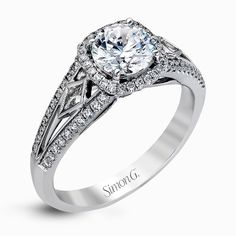 This elegant white gold ring features a lovely vintage style accentuated by .27 ctw of round cut white diamonds and .11 ctw of kite shaped diamonds. Print Page