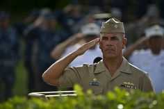 """U.S. Navy Capt. Jeffery James, Joint Base Pearl Harbor-Hickam (JBPHH), commander salutes as the American flag is raised to half staff at the """"Missing Man Memorial"""" at JBPHH, Hawaii during a Patriots Day ceremony to commemorate the 11th anniversary of the 9/11 terrorist attacks at the World Trade Center, Pentagon, and Flight 93. Sept. 11, 2012. (Department of Defense photo by U.S. Air Force Tech. Sgt. Michael R. Holzworth/Released)"""
