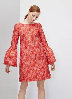 Ad 16. Vestido recto en tejido brocado de lúrex en un llamativo y elegante rojo geranio. Cuello redondo y manga larga con maxi volante desflecado.