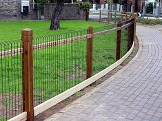 This is a nice example of natural wood posts to support ornamental woven wire fencing so that it is designed to weather naturally. By Heritage Fencing.