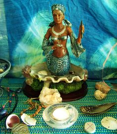 Ocean Goddess Yemaya altar with intensely dyed blue-green backdrop and woven altar cloth. Yemaya can be invoked to assist with: • Healing Spells, as she is the Great Healer • Protection Spells, as she is the Merciful Mother of All • Travelling Spells, especially travels over the sea • Dream Magic, as she is highly associated with the collective unconscious and prophetic dreams • Shapeshifting, as she is the Constantly Changing Woman • Female Rituals, to grant fertility, to bless the newborn…