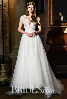 Brides.com: . Style 16-114, handcrafted appliques and netting dress over illusion bodice and skirt, all beaded with short cap sleeves, Berta
