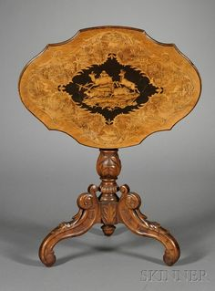 South German Marquetry-inlaid and Carved Walnut Tilt-top Table, early 20th century, shaped top inlaid with a central scene of deer bounding across a landscape and with scrolling foliate borders, the stem and base carved with leaftips and fluting.