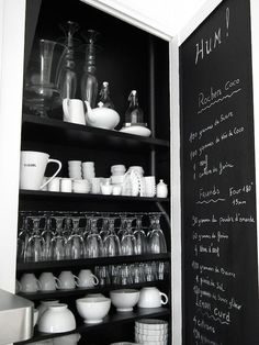 Black and white kitchen features pantry with chalkboard door opening to stacked shelves.