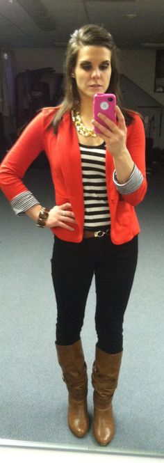 red blazer with a  striped black and white tank, black pants, burnt brown belt and boots, and chunky gold necklace.