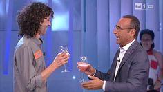 """Carlo Conti brinda con un concorrente vincitore della """"ghigliottina"""" nel quiz televisivo """"L' eredità""""."""