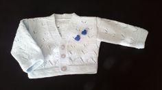 Detalle de chaquetita para bebé con dos patitos azules