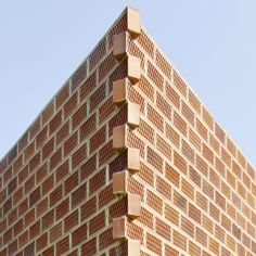 The perforated brick walls of this triangular house in Barcelona overlap at the corners.