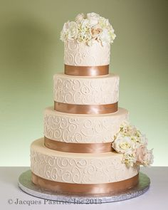 Blush-colored cake with scrollwork and pale pink and cream flowers
