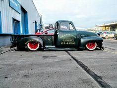 Slammed shop truck built from a Five Window Advanced Design chevy truck on wide white walls and red wheels with a rusty and patina finish.