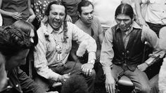 """Original caption: """"September 17, 1974-St. Paul, MN: American Indian Movement (AIM) leaders Russell Means (L, seated) and Dennis Banks (seated wearing vest) sing an AIM victory song with other AIM members at a rally. The victory rally was held after charges were dismissed against Banks and Means in the eight-month-old Wounded Knee trial."""""""