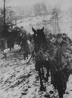 A column of German soldiers during a snowfall on the outskirts of the village on the Eastern Front