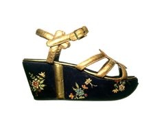 Salvatore Ferragamo, sandal, 1938. Gilded kidskin upper. Wedge-shaped mid-sole covered in black satin, hand-painted with floral patterns