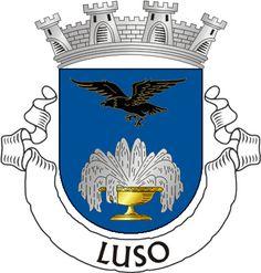 """Heraldry of the World Civic heraldry of Portugal - Brasões dos municípios Portugueses - Escudo de azul, fonte de ouro repuxando de prata; em chefe, águia voante de negro, realçada e perfilada de ouro. Coroa mural de prata de quatro torres. Listel branco, com a legenda a negro: """"LUSO""""."""