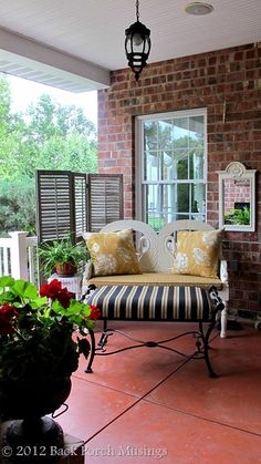 Haven't they made a glorious spot out of this porch area? The shutters used a backdrop is great as is the contrast of colors on the pillows and bench. Love! LJH