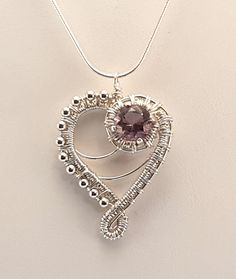 Amethyst and sterling silver heart pendant. Amethyst is 10 mm faceted round cut. Self collected from Diamond Hill Mine in S.C. Set and wrapped in sterling silver by me.