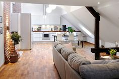 A modern penthouse apartment in Sweden features an area of 85 square meters filled with compact spaces. The complex architecture makes for an interesting inteiror design with partly exposed brick and rounded windows. The slanted ceiling makes the apartment look smaller but the designers managed to use every inch of space very efficiently.