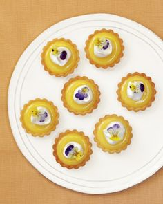 Lemon tartlets topped with a dollop of honey cream and edible viola tricolor petals.