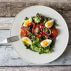 Traditional tuna nicoise salad with red onion, tomatoes, pepper, fine beans, dried black olives and egg.
