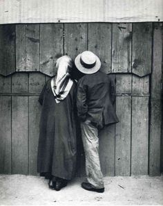 """Couple Looking Through The Slats At The Circus, Budapest 1920"" by André Kertész."