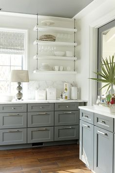 pretty, grey cabinets with warm wood floor. I like the repeat of the Grey on the ceiling and door. With carerra marble/quarts countertops. I also like the idea of white walls with white cabinetry above, or open white shelving.