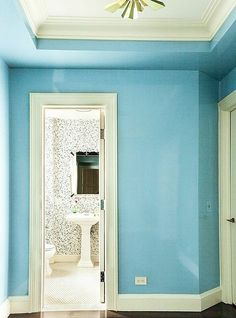 Sky blue entry hall with white trim and a brass flush mount light.