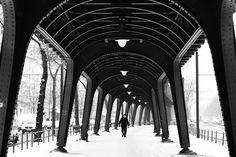 Under the bridge 2 - Winter in Berlin. There is snow on the roads. A man walks alone under the subway bridge in Berlin Schönhauser Allee. Black white street photography from Berlin.