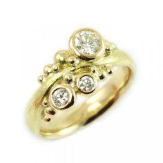 Bølgering med diamanter - Fire små diamanter træder dansen om den smukke 0,2 ct centersten, I et symmetrisk, men delikat bølget design, der synes at løfte de blanke kugler op og giver dem ekstra liv. En ganske særlig og lidt anderledes forlovelses- eller vielsesring.   Kreamarked.dk