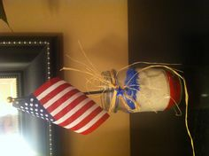 4th of July centerpiece. Use a mason jar to put red, white, and blue sand in it. Then stick a small flag in the center.
