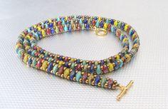 Hermoso abrigo pulsera de múltiples colores de granos superduo. Rojo, amarillos, azul y verdes los granos se combinan para una pulsera funky y chic que se puede usar con muchas cosas diferentes. I esto es para la mujer que quiere ser diferente y disfruta de un look boho/hippie. Pueden usarse solas o apilado con otras pulseras. Envuelve 3 veces un promedio 7 1/2 muñeca (22 1/2 de largo) oro pulseras